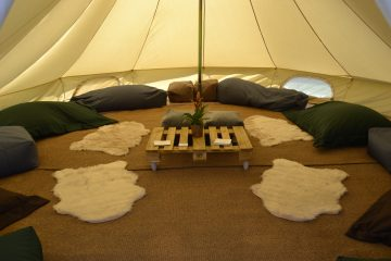 Inside a bell tent at a music festival with comfy cushions
