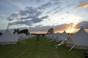 Long group of bell tents for friends at a music festival