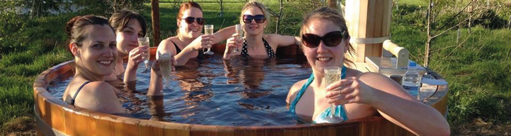 Ladies in a hot tub drinking Champagne at their Hen Camp