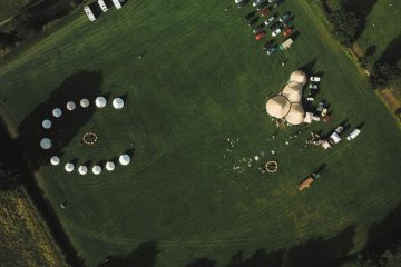 Aerial view of a bell tent village set up by Tinkers Bells