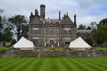 Large castle behind two bell tents for a wedding