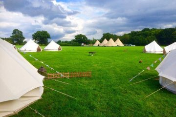Bright green grass with bell tents in an open field