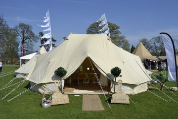 A front view of an emperor bell tent in a warm countryside