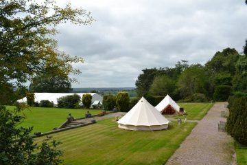 Bell tents on the front grass of the large castle